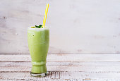 a glass of green tea smoothie on white wooden board