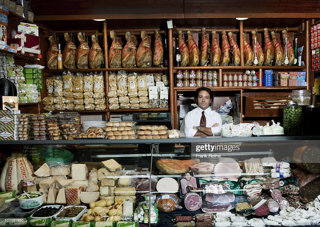 a grocer behind his counter in his shop : Stock Photo