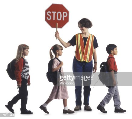 a group of children walk in a line while assisted by a crossing guard