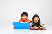 a group of Cute little asian boy and girl reading book while sitting or lying over white backgrounda group of Cute little asian boy and girl reading book while sitting or lying over white background