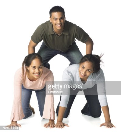 a group of three ethnic siblings form a small human pyramid as they play around : Stock Photo
