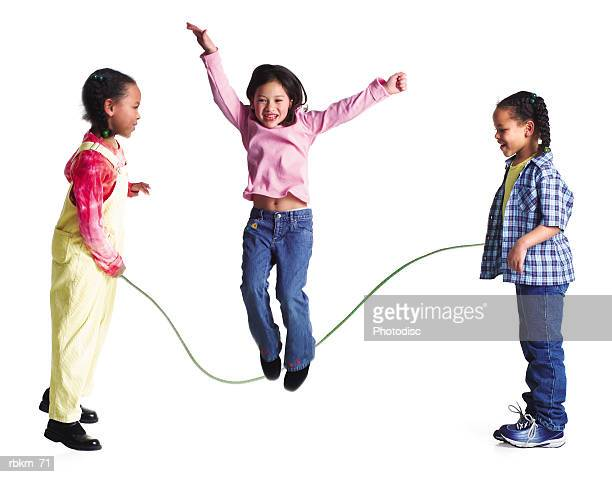 a group of three girls play jump rope together