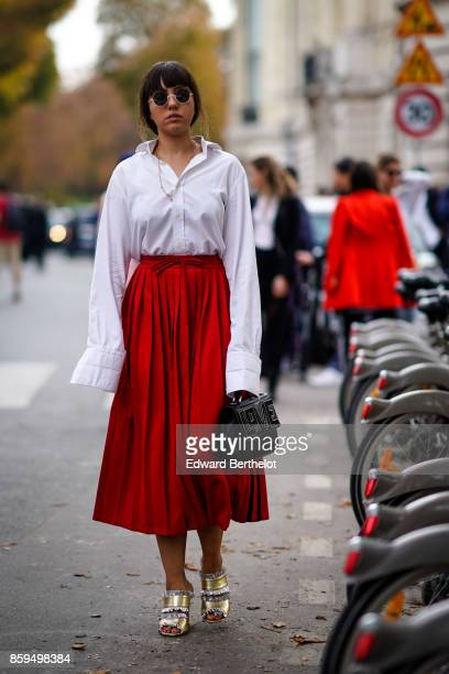 a guest wears sunglasses a white longsleeved shirt a long red pleated skirt a black studded bag silver and gold color shoes outside the Rochas show...