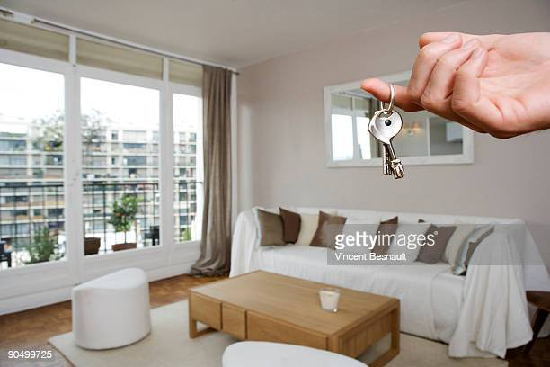a hand holding a key in a apartment