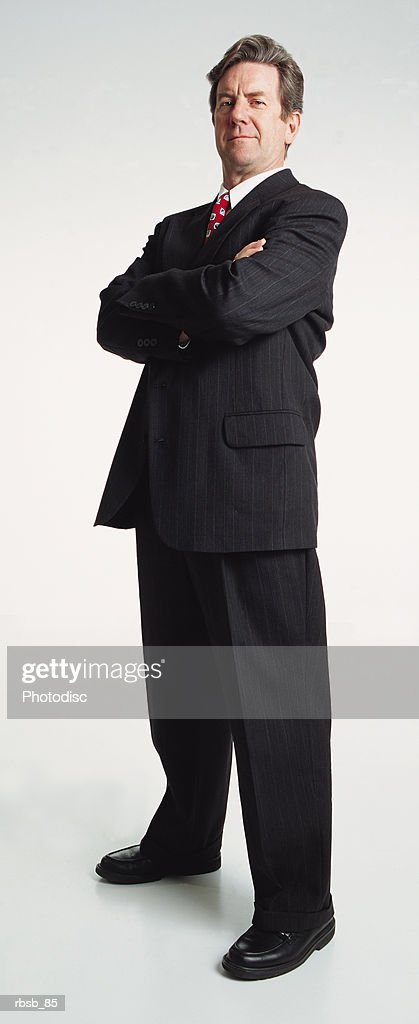 a handsome middle aged caucasian businessman with dark hair dressed in a dark suit looking into the camera with his arms crossed : Stock Photo