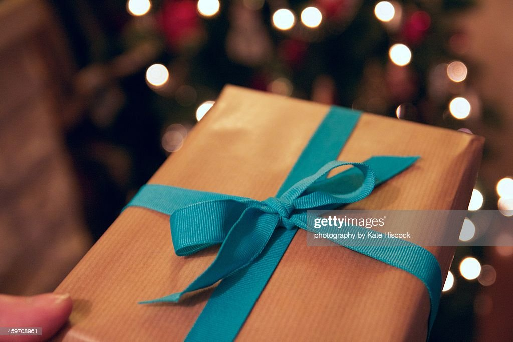 a holiday gift wrapped in brown paper and ribbon