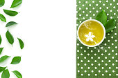 Top view shot of a hot cup of tea with green leaf decoration  with green napkin on white background , Organic green Tea ceremony time concept