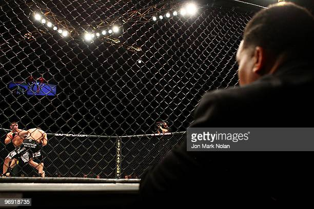 a judge watches on as UFC fighter George Sotiropoulos battles UFC fighter Joe Stevenson during their Ultimate Fighting Championship lightweight fight...