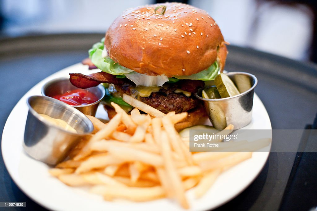 a large burger served with fries and cucumber : Stock Photo