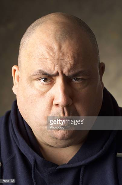 a large sized caucasian man wearing a blue sweatshirt has a shaved head and is scowling with pursed lips