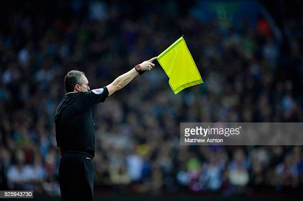 a linesman / assistant referee holds his flag to show offside