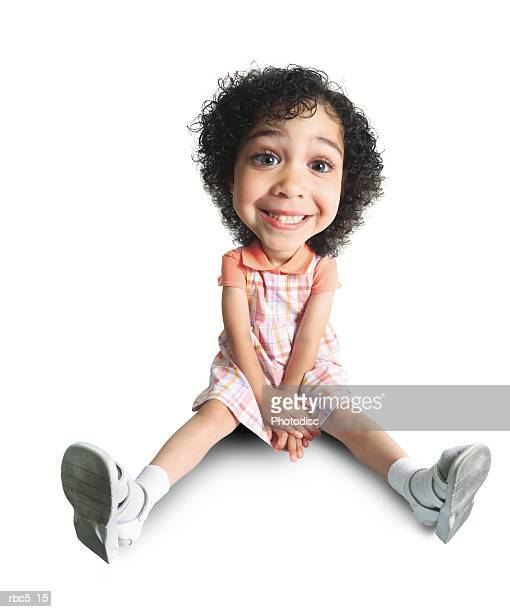 a little african american girl sits on the floor with her hands crossed in her lap and grins cheesily at the camera
