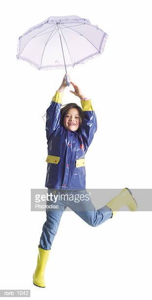 a little asian girl in rain gear and an umbrella jumps up playfully into the air