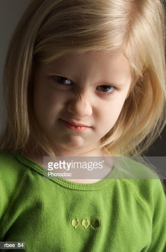 a little blond girl in a green shirt scrunches her nose in an expression of annoyance : Stock Photo