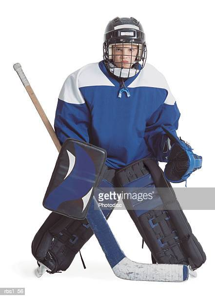 a little caucasian boy dressed in a hockey uniform stands with legs apart scowling through his goalie mask