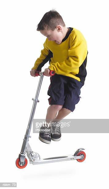 a little caucasian boy in a yellow shirt jumps up while riding his scooter