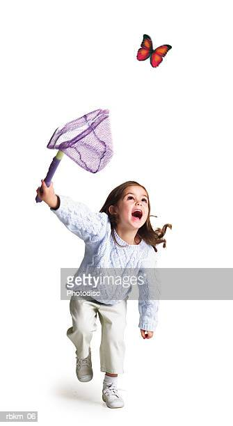 a little caucasian girl runs with a net trying to catch a butterfly
