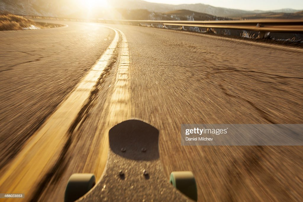 POV of a longboard skateboard going down the road.