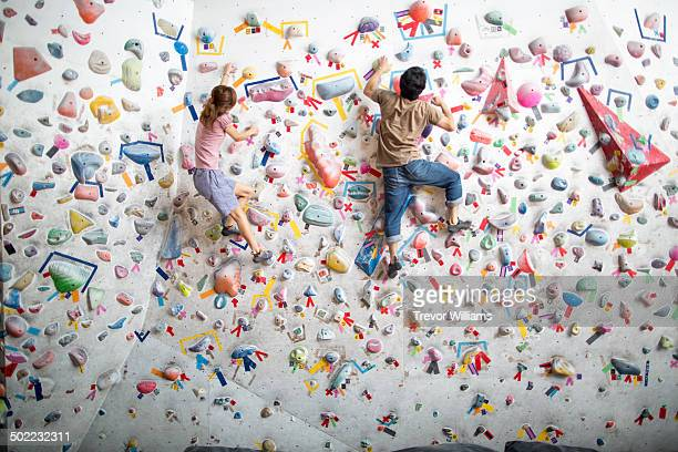 a man and a woman climb at a bouldering gym