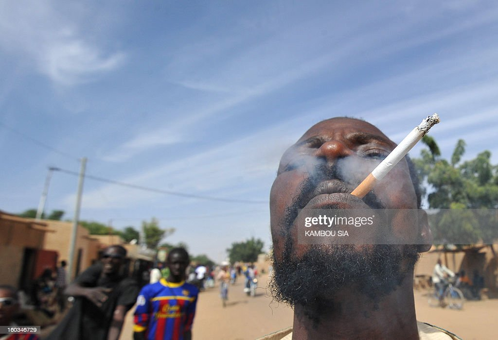 A a man enjoys smoking a cigarette as he celebrates on January 29, 2013 in Ansongo, a town south of the northern Malian city of Gao, Niger troops entering the city. Troops from Niger and Mali on January 29 entered Ansongo, which along with Gao was recaptured by French-led soldiers over the weekend in a lightning offensive against radicals holding Mali's north. So far, just 2,000 African troops have been sent to Mali or neighboring Niger, many of them from Chad, to boost the French-led offensive which began on January 11 and led to the recapture of several towns, including Ansongo. AFP PHOTO / KAMBOU SIA