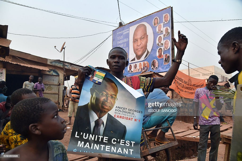 a man holds a campaign posters of Central African Republic second round presidential candidate Anicet Georges Dologuele (down) near one of Faustin Archange Touadera in a street of Bangui on February 10, 2016, ahead of the Febuary 14 presidential and legislatives elections. The deferred presidential run-off, delayed due to organisational problems, and postponed legislative election, rescheduled after annulment due to irregularities, have been widely seen as turning a page on the worst sectarian violence in the traditionally unstable and dirt poor nation. / AFP / ISSOUF SANOGO
