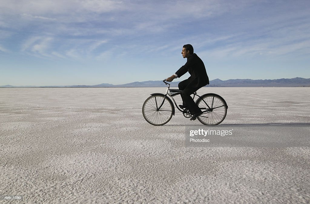 a man in a business suit rides his bike through the open nothingness of a desert