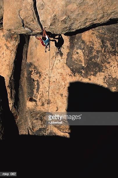 a man is hanging from the overhang of a cliff face which is partially hidden in shadow