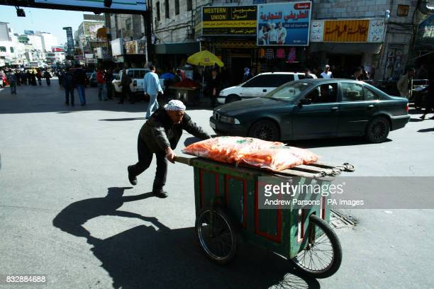 a man pushes a trolley through the main square in Ramallah