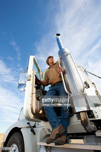 a man standing on the step of the cab of his truck
