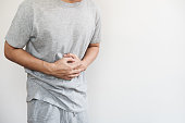 a man touching his stomach, stomach pain and others stomach disease concept, on white background