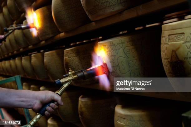 a man works marking the form of Grana Padano in aging warehouses of Parmesan and Grana Padano on January 01 2012 in Fiorenzuola d'Arda Italy The...