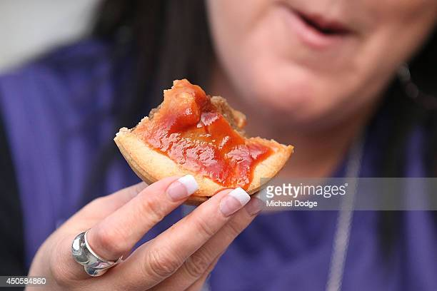 a meat pie is eaten by a fan during the round 13 AFL match between the Richmond Tigers and the Fremantle Dockers at Melbourne Cricket Ground on June...