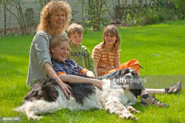 a mother and her children are sitting in the garden with the family dog fondling her families people children kids woman son pets animals boys girl