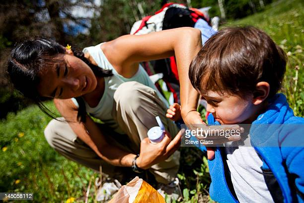 a mother applies sunscreen to her son as they sit in a grassy meadow, with their backpacks behind them, on the Williams Creek Trail (trail number 587) during the beginning of their family backpacking trip.