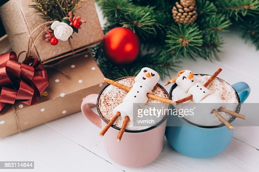 una taza con chocolate caliente en una mesa de madera con un hombre malvavisco que está descansando en una taza : Foto de stock