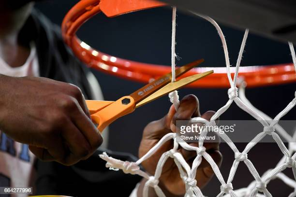 a North Carolina Tar Heels basketball player cuts a piece of the net during the 2017 NCAA Men's Final Four National Championship game against the...