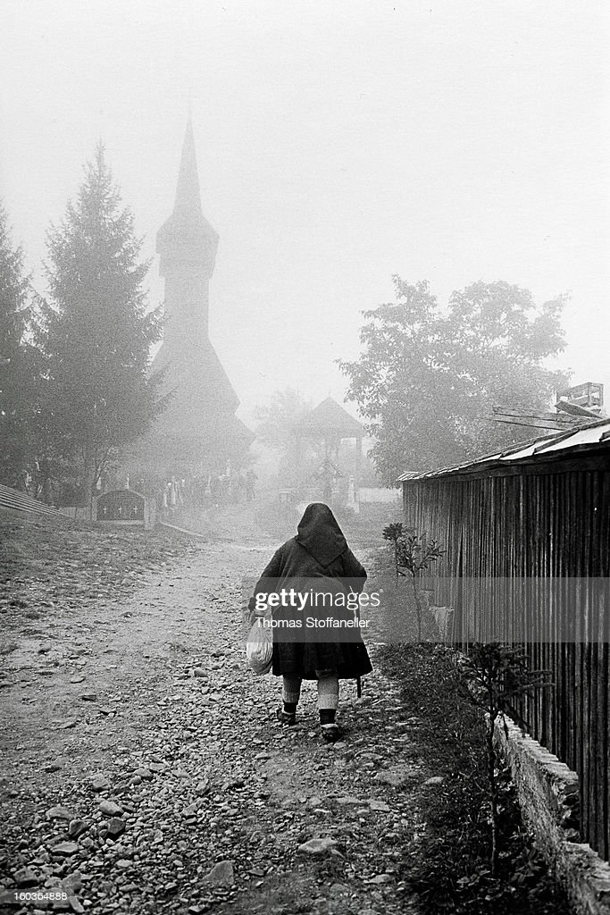 CONTENT] a old woman at a foggy morning walk to church in Maramures, Romania