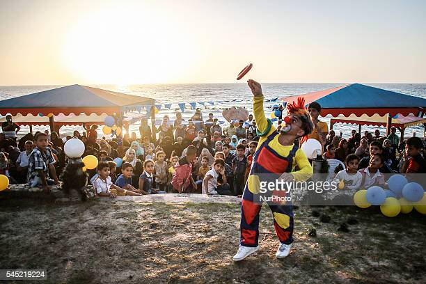 a palestinian clown performing some acrobatic movements during an Iftar attended by people fasting in Ramadan in Rafah city on 24 june 2106