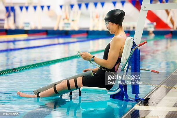 a paraplegic woman is lowered into the swimming pool on a lift and prepares to swim