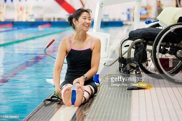 a paraplegic woman sits at the edge of a swimming pool on a lift beside her wheelchair and prepares to swim