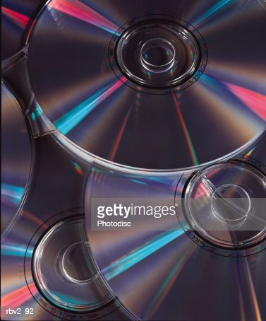 a pile of compact disks giving off blue and pink lights : Stock Photo