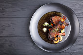 portion of tasty chicken stew - thigh and drumstick braised with wine, herbs, mushrooms and vegetables served on black plate on wooden table, festive Burgundian dish - Coq Au Vin, view from above