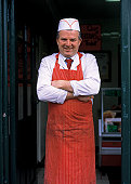 a portrait of a bakery chef standing in a doorway