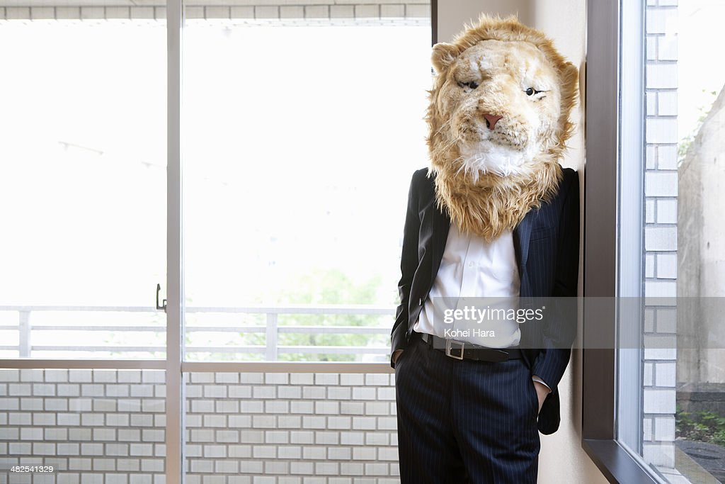 A business man wearing a lion costume leans on the wall at office.