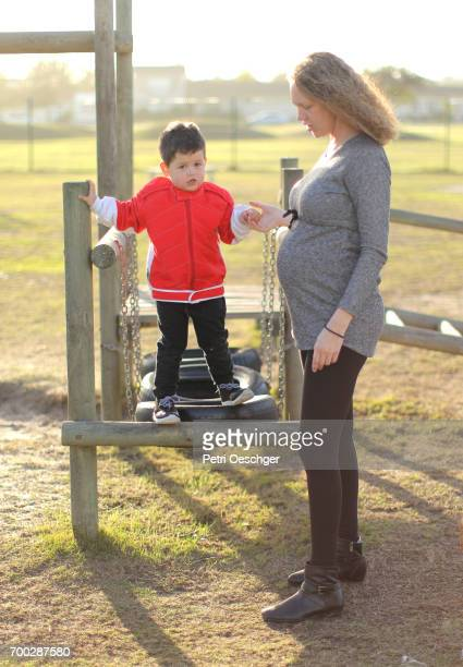 a pregnant Mother and her young son playing in the park.
