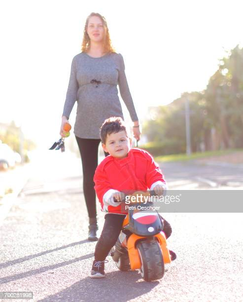 a pregnant Mother walks with her young son as he rides his scooter.