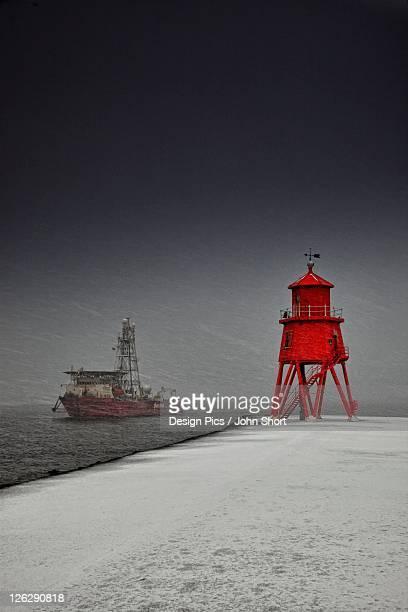 a red lighthouse along the coast in winter with a boat off the shore in the water
