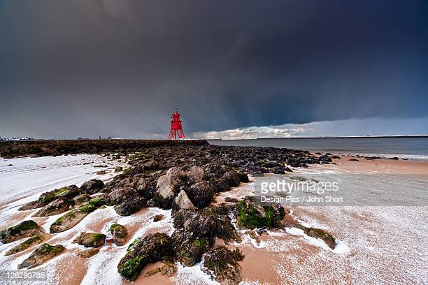 a red lighthouse along the coast under a stormy sky