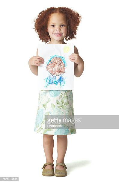 a redheaded female child in a green floral dress stands proudly with some of her atwork