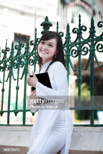 a school girl smiling stand agaist green fence : Stock Photo